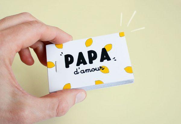 main qui tient un cadeau personnalisé fête des pères jaune