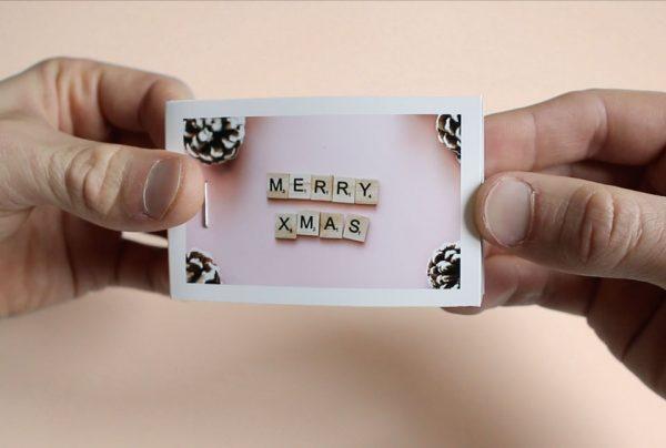 mains qui tiennent un flipbook merry xmas